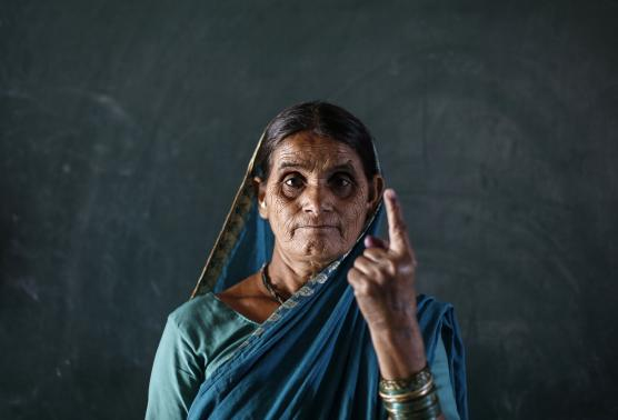 A woman shows her ink-marked finger after voting inside a polling station in the village of Kamshet, in the western Indian state of Maharashtra